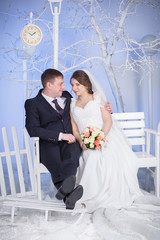 the bride and groom sit on the bench
