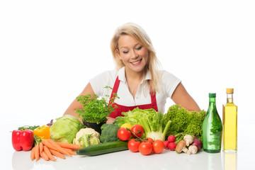 Blonde Frau schaut auf viele verschiedene Gemüsesorten