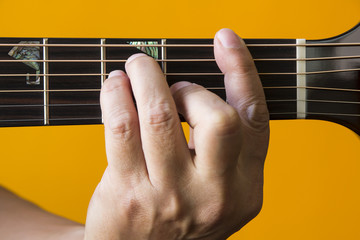 Hand performing F chord on guitar