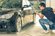 Man washing his new car