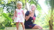 small blonde child play with soap bubbles with mother blowing