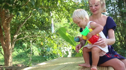 little blonde girl playing with small toy car and sits mother