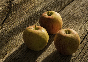 Drei Äpfel auf altem Holz