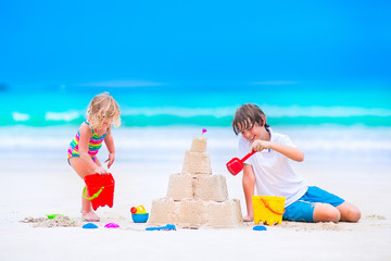 Happy kids building sand castle on the beach