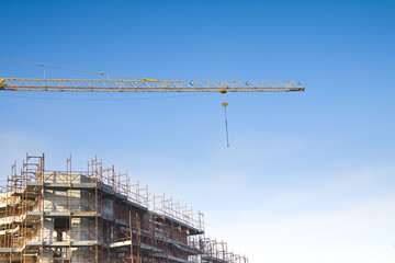Tower crane in a blue background con scaffolding to work on the