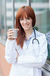 red hair female doctor standing outside while having a cappuccin