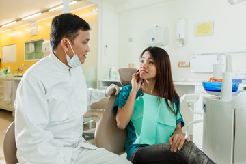 asian woman is explaining her dentist that she has pain