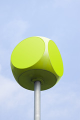 Green cube with rounded edges against sky background