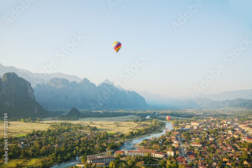 Foto op Aluminium Ballon scene of flying hot air balloon over city