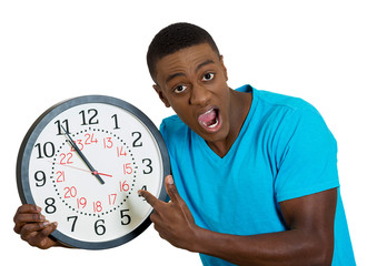 man holding wall clock, stressed pressured by lack of time