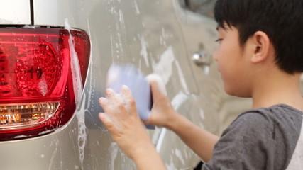 Asian cute boy washing car . Child helping family clean big car.