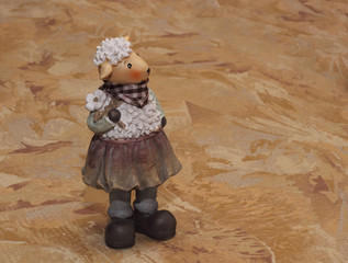 Ceramic sheep statuette on the textile background