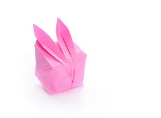 Pink origami bunny on white background