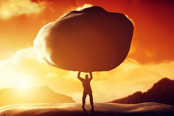 Man lifting a huge rock. Concept of strength, ballast, power