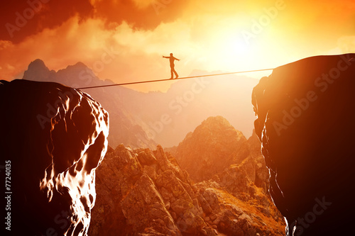 Leinwanddruck Bild Man walking and balancing on rope over precipice in mountains