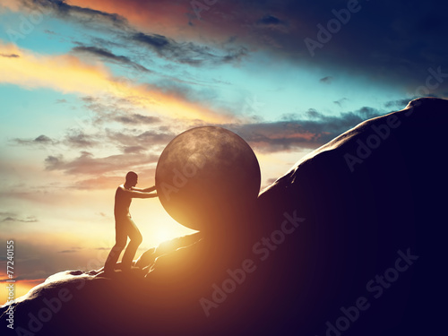 Sisyphus metaphor. Man rolling huge concrete ball up hill. - 77240155