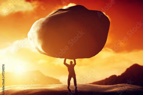 Leinwandbild Motiv Man lifting a huge rock. Concept of strength, ballast, power