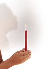 Female silhouette holding a candle in hands