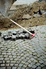 Pick axe near granite blocks near street reparation