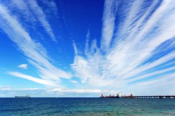 Petroliera al pontile e cielo pieno di nuvole