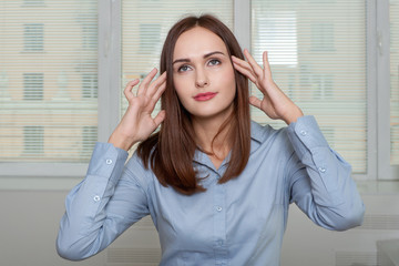 Woman in office holds hands behind his head