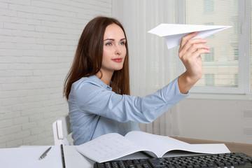 Girl throwing paper airplane