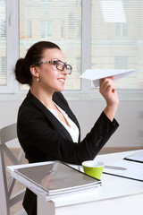 Woman in a suit sitting at table in office throwing paper airpla