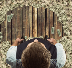Man standing  surrounded with dollars