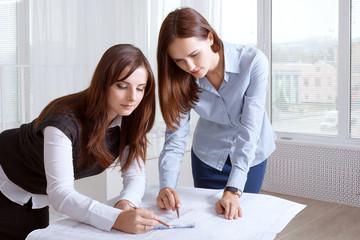Female architects studying blueprints and make notes