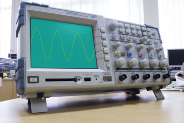 Oscilloscope with sine wave illustration