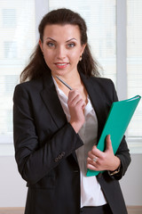 Girl holding a green folder and pen touching her chin