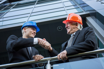 Engineers in helmets shaking hands
