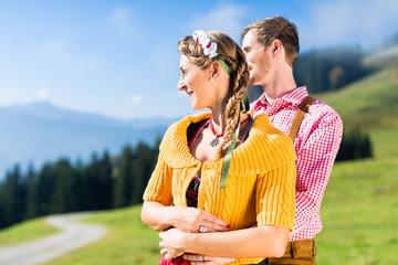 Paar in Tracht im Urlaub auf Alpen Berggipfel