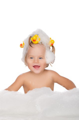 Smiling girl with ducks and soap foam