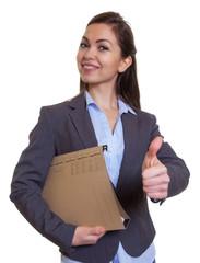 Geschäftsfrau im grauen Blazer mit Akte zeigt Daumen