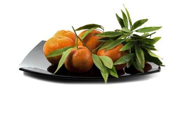 tangerines on a big black plate