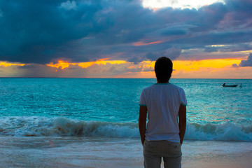 Young man enjoying sunset during beach vacation