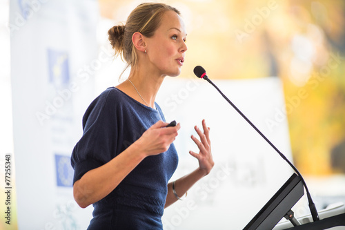 Pretty, young business woman giving a presentation - 77255348