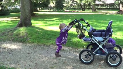 Kind spielt mit Kinderwagen
