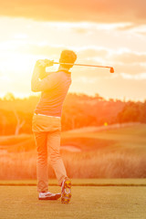 Golf player tee off at sunset