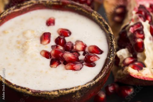 Dish of banana millet breakfast pudding with pomegranate - 77264753