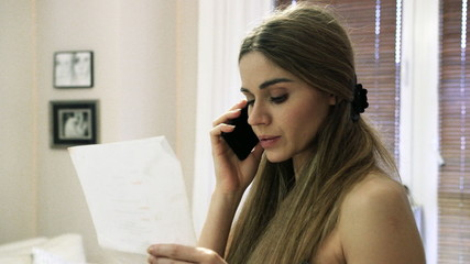 Stressed young woman holding letter and talking cell phone.