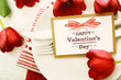 Dinner table setting with Valentines message and red tulips - 77270514