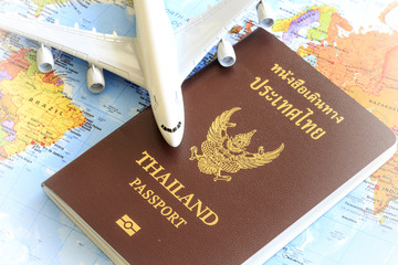Toy plane resting on a thailand passport and world map