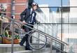 businessman in crash helmet carrying bicycle down steps - 77274571