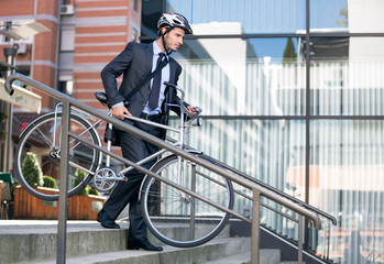 businessman in crash helmet carrying bicycle down steps