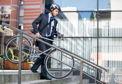 canvas print picture businessman in crash helmet carrying bicycle down steps