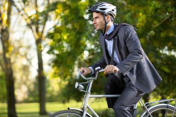 man in a business suit on  bicycle