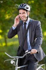 young businessman wearing bike helmet and using mobile phone