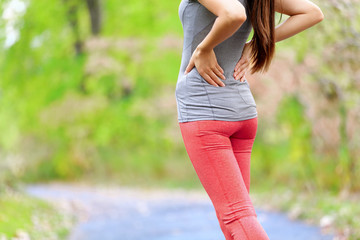 Back pain - Athletic running woman with back injury